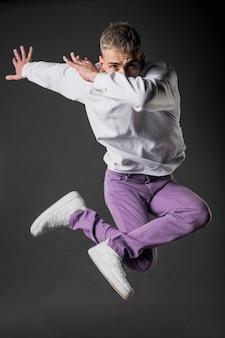 Vooraanzicht van mannelijke danser in paarse jeans en sneakers poseren mid-air