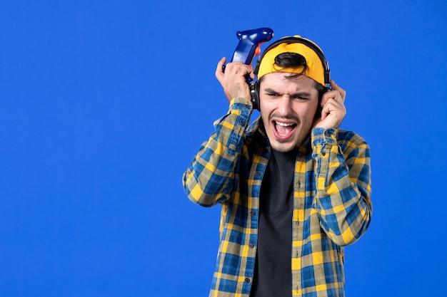 Vooraanzicht van mannelijke gamer met gamepad en koptelefoon die videogame speelt op blauwe muur