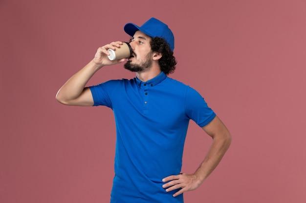 Vooraanzicht van mannelijke koerier in blauw uniform en pet die koffie drinken op roze muur