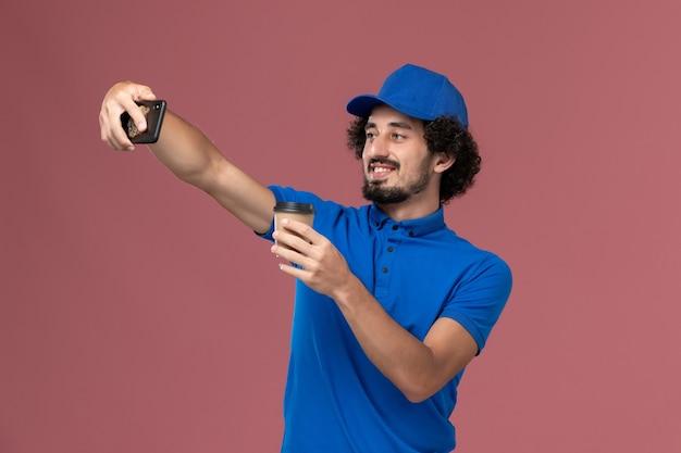 Vooraanzicht van mannelijke koerier in blauw uniform en pet met bezorging koffiekopje op zijn handen en het nemen van foto op roze muur