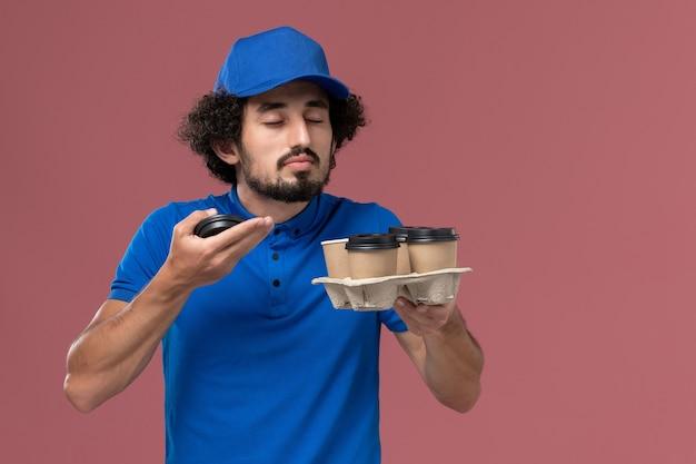 Vooraanzicht van mannelijke koerier in blauw uniform en pet met bezorging koffiekopjes op zijn handen ruikende geur op lichtroze muur