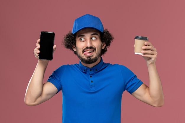 Vooraanzicht van mannelijke koerier in blauw uniform en pet met koffiekopje en telefoon op zijn handen op roze muur