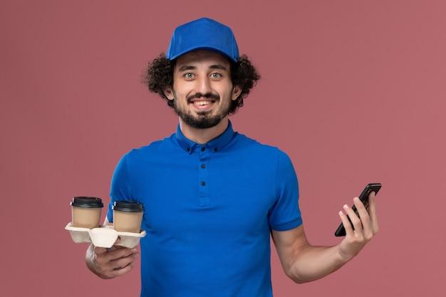 Vooraanzicht van mannelijke koerier in blauw uniform en pet met koffiekopjes voor levering en werktelefoon op zijn handen op de roze muur