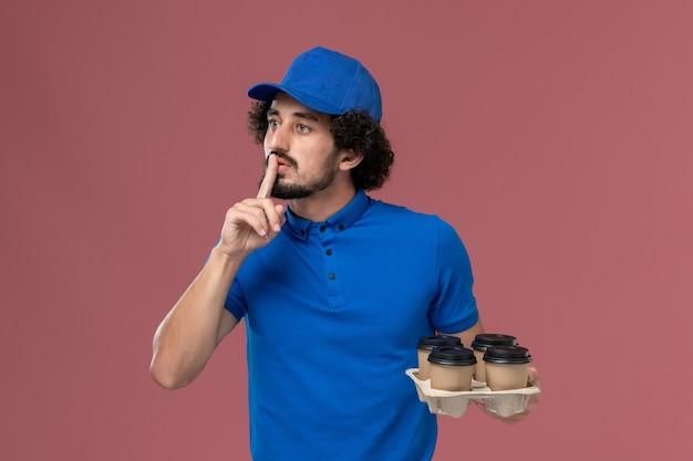 Vooraanzicht van mannelijke koerier in blauw uniform en pet met levering koffiekopjes op zijn handen en vragen stil te zijn