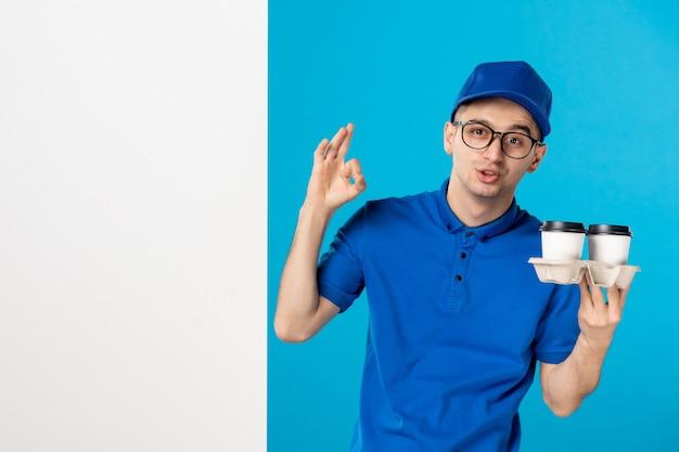 Vooraanzicht van mannelijke koerier in blauw uniform met koffie op het blauw
