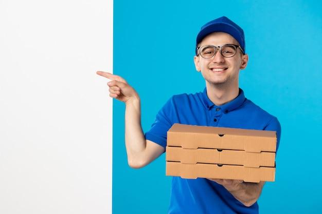 Vooraanzicht van mannelijke koerier in blauw uniform met pizza op blauw