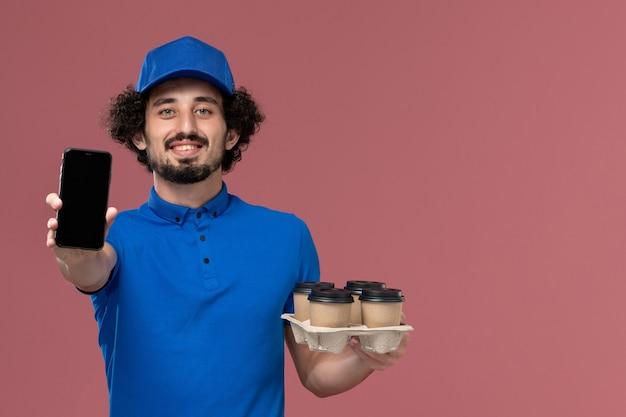 Vooraanzicht van mannelijke koerier in blauwe uniforme pet met koffiekopjes levering op zijn handen en zijn werktelefoon op roze muur