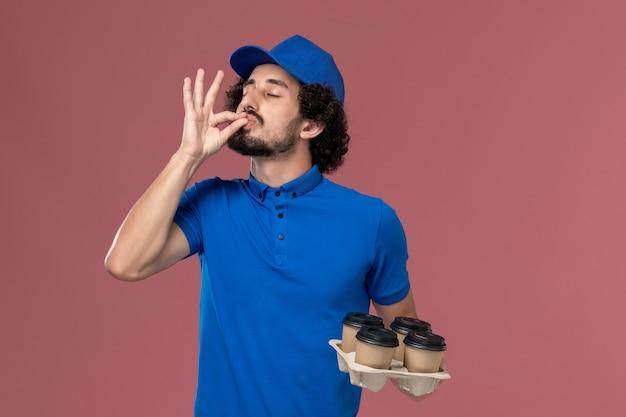 Vooraanzicht van mannelijke koerier in blauwe uniforme pet met koffiekopjes levering op zijn handen op lichtroze muur