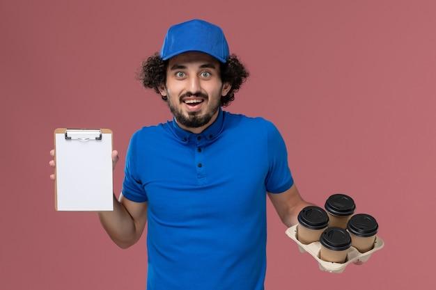 Vooraanzicht van mannelijke koerier in blauwe uniforme pet met koffiekopjes van de levering en blocnote op zijn handen die op roze muur glimlachen
