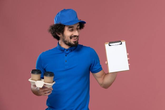 Vooraanzicht van mannelijke koerier in blauwe uniforme pet met koffiekopjes voor levering en blocnote op zijn handen op roze muur