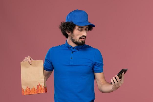 Vooraanzicht van mannelijke koerier in blauwe uniforme pet met levering voedselpakket op zijn handen met behulp van telefoon op de roze muur