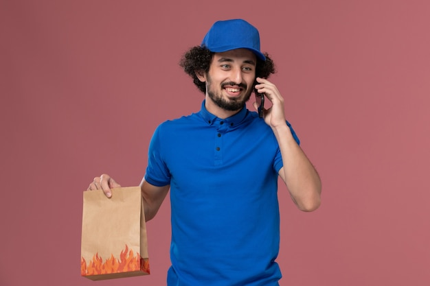 Vooraanzicht van mannelijke koerier in blauwe uniforme pet met levering voedselpakket op zijn handen praten aan de telefoon op de roze muur