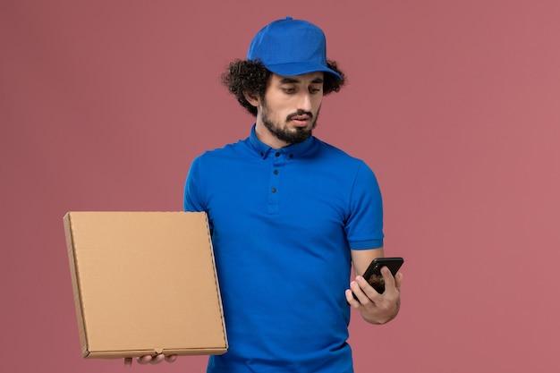 Vooraanzicht van mannelijke koerier in blauwe uniforme pet met voedseldoos en telefoon op zijn handen op de lichtroze muur