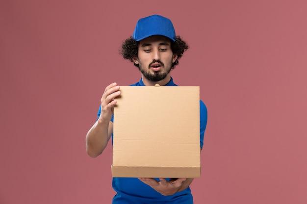Vooraanzicht van mannelijke koerier in blauwe uniforme pet met voedseldoos op zijn handen openen op lichtroze muur