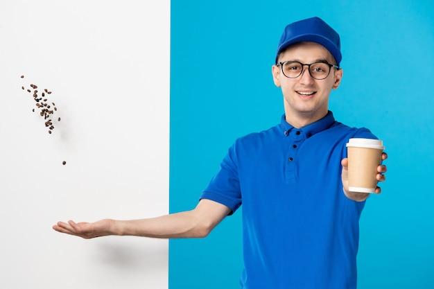 Vooraanzicht van mannelijke koerier in uniform met koffie op blauw