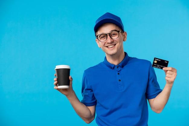 Vooraanzicht van mannelijke koerier met koffie en bankkaart op blauw