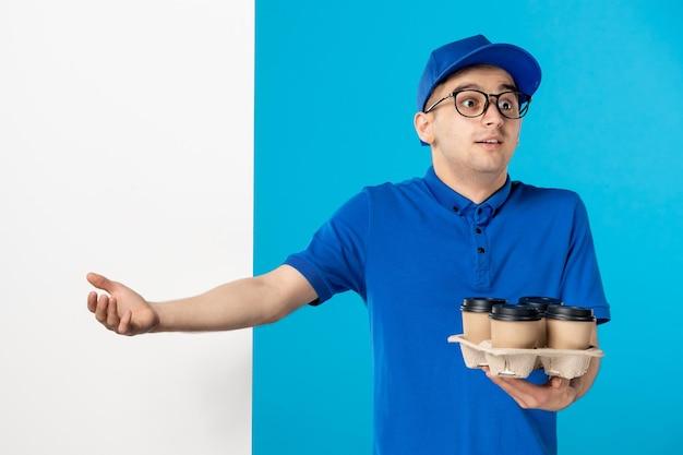 Vooraanzicht van mannelijke koerier met koffie op het blauw