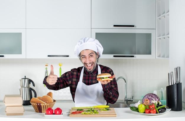 Vooraanzicht van mannelijke kok die duimen opgeeft en hamburger omhoog houdt die achter de keukentafel staat