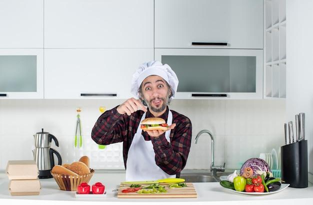Vooraanzicht van mannelijke kok die een grote hamburger omhoog houdt die achter de keukentafel staat