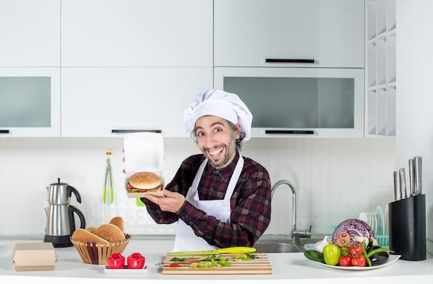 Vooraanzicht van mannelijke kok die hamburger omhoog houdt die achter keukentafel in moderne keuken staat