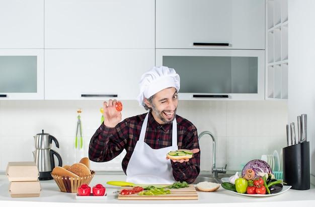 Vooraanzicht van mannelijke kok die met knipperend oog hamburger maakt die achter de keukentafel staat