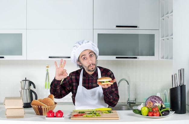 Vooraanzicht van mannelijke kok die ok gebarend hamburger omhoog houdt die achter keukentafel staat