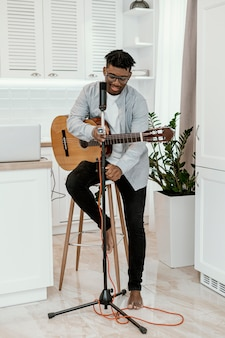 Vooraanzicht van mannelijke musicus die thuis gitaar met microfoon speelt