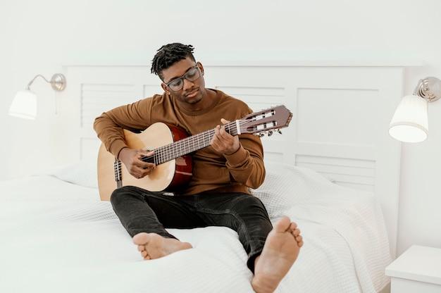 Vooraanzicht van mannelijke musicus die thuis gitaar op bed speelt