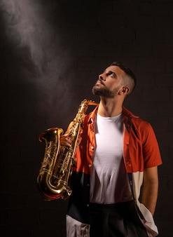 Vooraanzicht van mannelijke muzikant die naar schijnwerper kijkt terwijl hij saxofoon vasthoudt