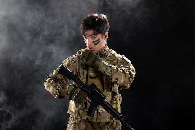 Vooraanzicht van mannelijke soldaat in camouflage die een geweer op een zwarte muur richt