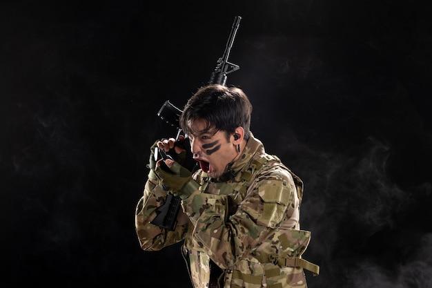 Vooraanzicht van mannelijke soldaat met geweer schreeuwend door walkie-talkie zwarte muur