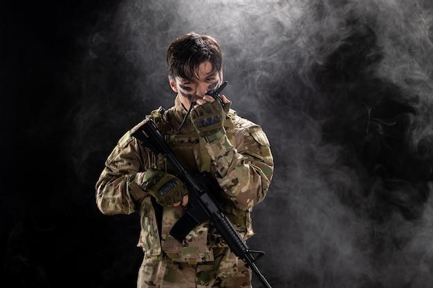 Vooraanzicht van mannelijke soldaat met machinegeweer met behulp van walkie-talkie zwarte muur