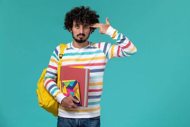 Vooraanzicht van mannelijke student die de gele dossiers van de rugzakholding en voorbeeldenboek op blauwe muur draagt