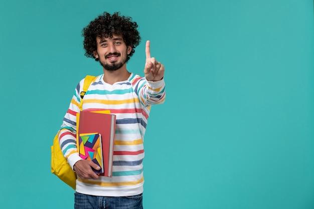 Vooraanzicht van mannelijke student die de gele dossiers van de rugzakholding en voorbeeldenboeken draagt die op blauwe muur glimlachen