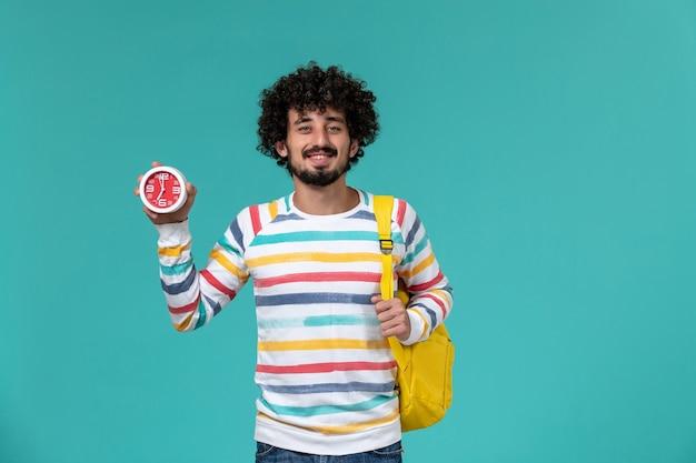 Vooraanzicht van mannelijke student die de gele klokken van de rugzakholding op de lichtblauwe muur draagt