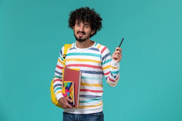 Vooraanzicht van mannelijke student die gele de dossierspen en voorbeeldenboek van de rugzakholding op de blauwe muur dragen