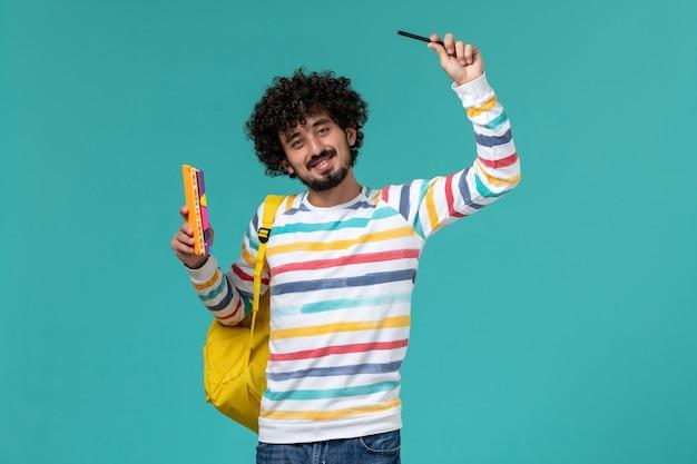 Vooraanzicht van mannelijke student die gele de voorbeeldenboeken van de rugzakholding op de blauwe muur draagt