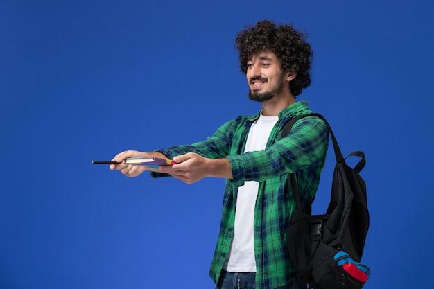 Vooraanzicht van mannelijke student die het zwarte voorbeeldenboek en de pen van de rugzakholding dragen die op blauwe muur glimlachen