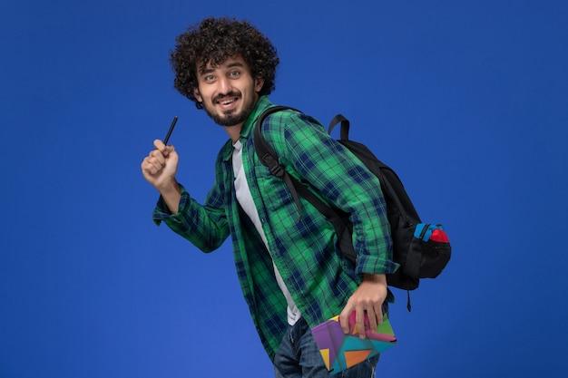 Vooraanzicht van mannelijke student die het zwarte voorbeeldenboek en de pen van de rugzakholding dragen die op blauwe muur lopen