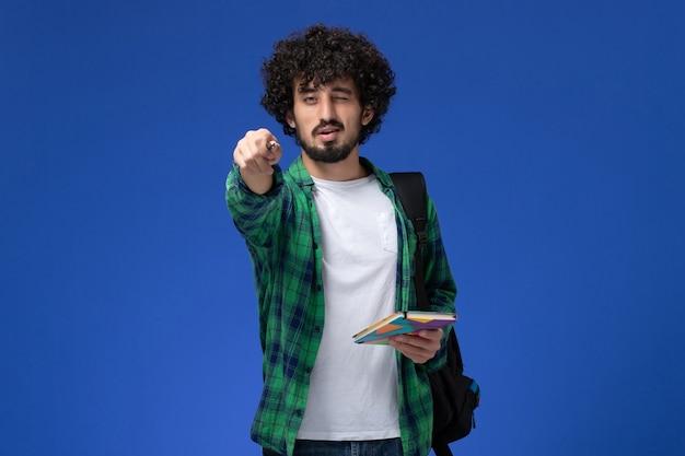 Vooraanzicht van mannelijke student die het zwarte voorbeeldenboek en de pen van de rugzakholding op de blauwe muur dragen