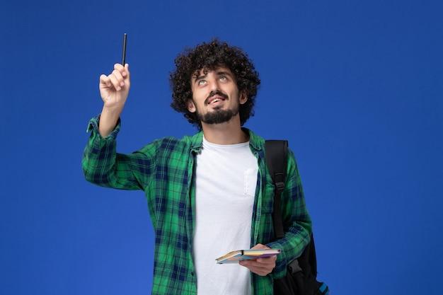 Vooraanzicht van mannelijke student die het zwarte voorbeeldenboek van de rugzakholding draagt en aan blauwe muur denkt