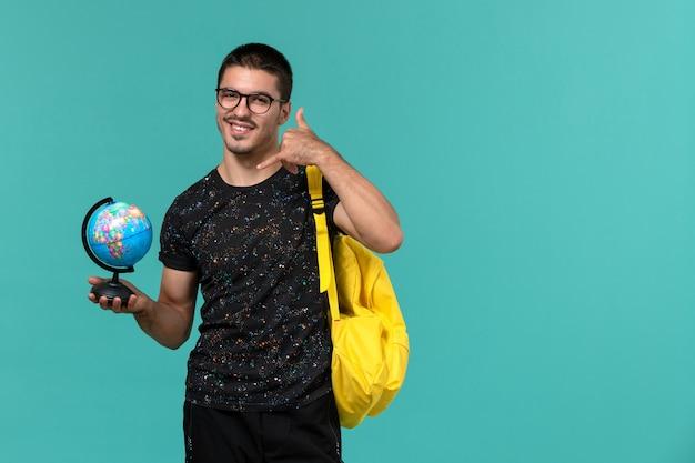 Vooraanzicht van mannelijke student die in donkere t-shirt gele rugzak kleine bol met glimlach op blauwe muur houdt