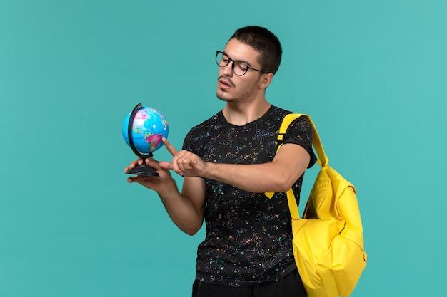 Vooraanzicht van mannelijke student die in donkere t-shirt gele rugzak kleine bol op blauwe muur houdt