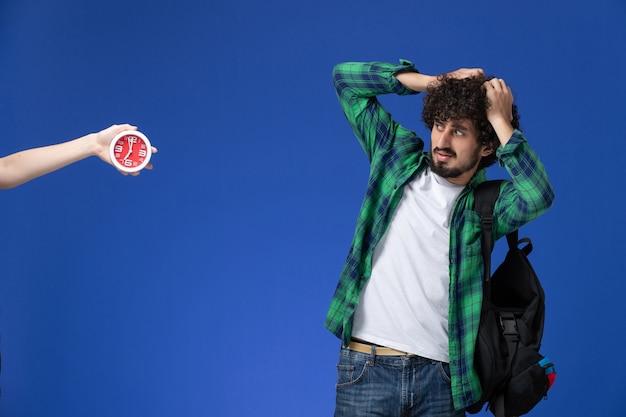 Vooraanzicht van mannelijke student die zwarte rugzak draagt die met verwarde uitdrukking op de lichtblauwe muur stelt