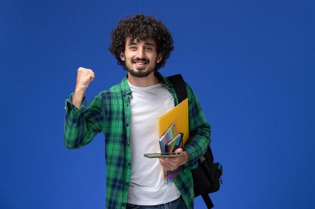 Vooraanzicht van mannelijke student die zwarte rugzak draagt die voorbeeldenboek en dossiers houdt die zijn telefoon op lichtblauwe muur gebruiken