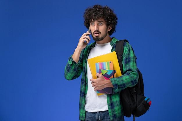 Vooraanzicht van mannelijke student die zwarte rugzak draagt die voorbeeldenboeken en dossiers houdt die aan de telefoon op lichtblauwe muur spreken
