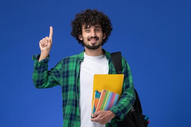 Vooraanzicht van mannelijke student die zwarte rugzak draagt die voorbeeldenboeken en dossiers op de blauwe muur houdt