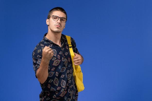 Vooraanzicht van mannelijke student in donker katoenen overhemd die gele rugzak dragen die bedreigend op lichtblauwe muur stellen