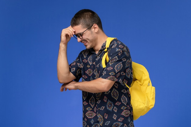 Vooraanzicht van mannelijke student in donker katoenen overhemd die gele rugzak dragen die op lichtblauwe muur lachen