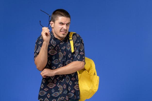 Vooraanzicht van mannelijke student in donker katoenen overhemd die gele rugzak dragen die op lichtblauwe muur stellen